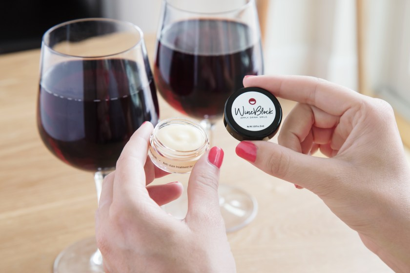 A woman is seen holding a container of WineBlock all-natural teeth balm next to 2 glasses of red wine
