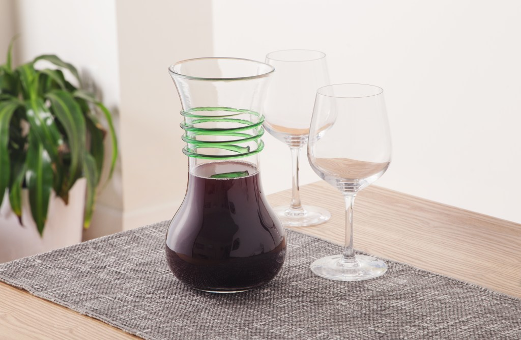 Red wine aerates in a Blenko Glass Company wine carafe accented with green glass spirals