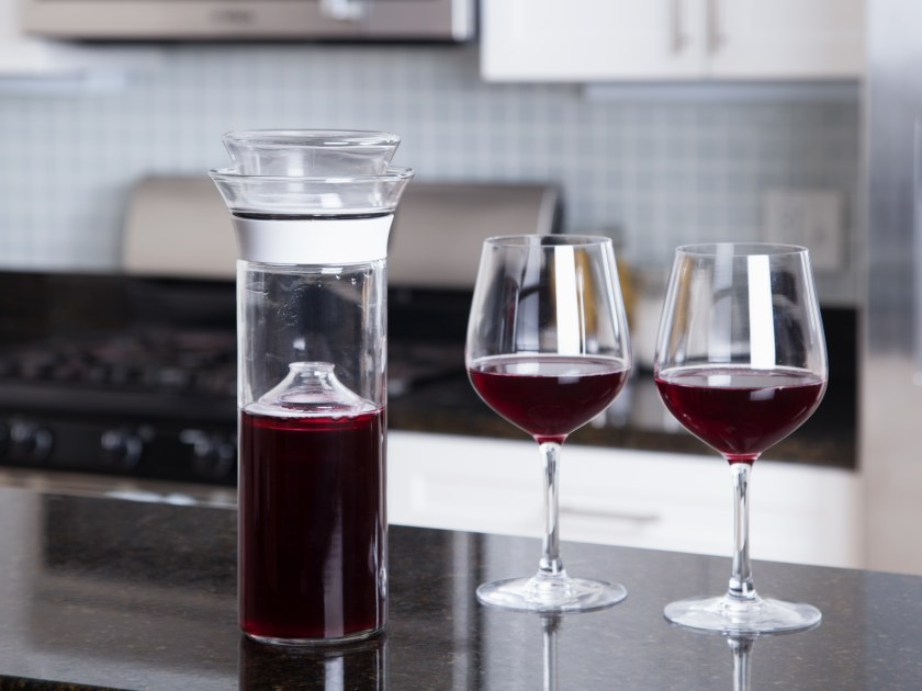 Red wine is seen poured into two glasses next to a wine saver carafe from Savino