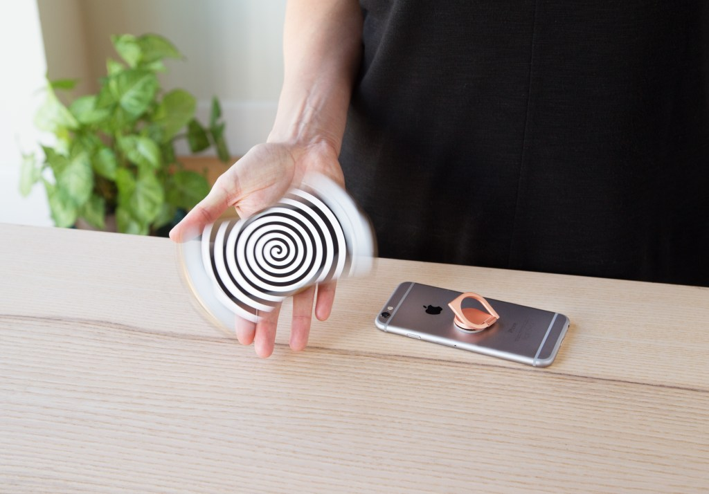A person is seen using a RingSpinner phone grip to spin their phone around