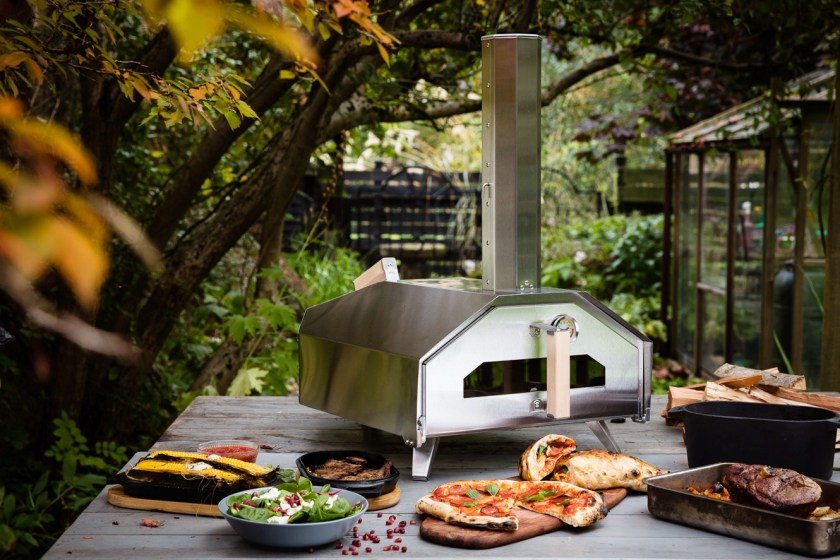 A variety of foods are seen cooked in front of the Uuni Pro multi-fueled outdoor pizza oven