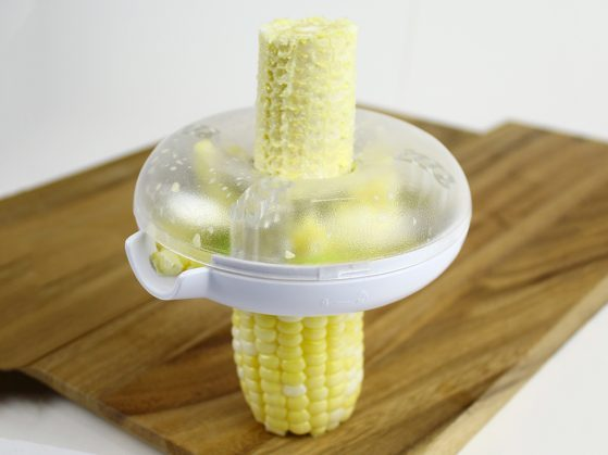 Corn is seen being trimmed off the cob with a ButterOnce corn peeler