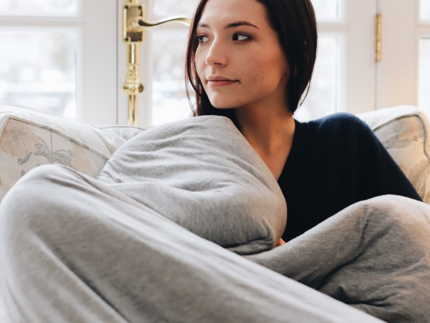 A woman is seen cozied up in an arm chair with a gray cooling weighted blanket from Hush Blankets