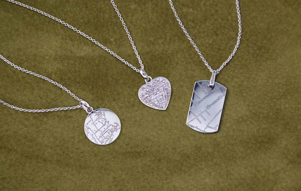 3 different sterling silver custom map pendant necklaces from A.JAFFE lay on a green background