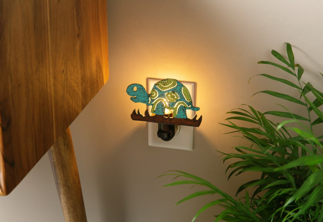 A recycled metal turtle night light from Whimsies can be seen plugged into a wall