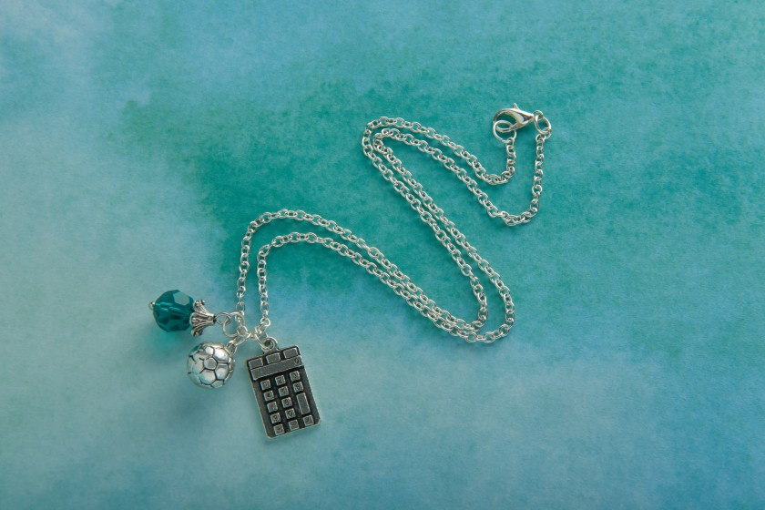 A Smart Girls Jewelry charm necklace features charms for soccer and a calculator with a teal bead