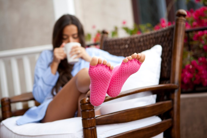 A woman is seen lounging outdoors wearing a pair of pink grippy toeless socks from Toezies