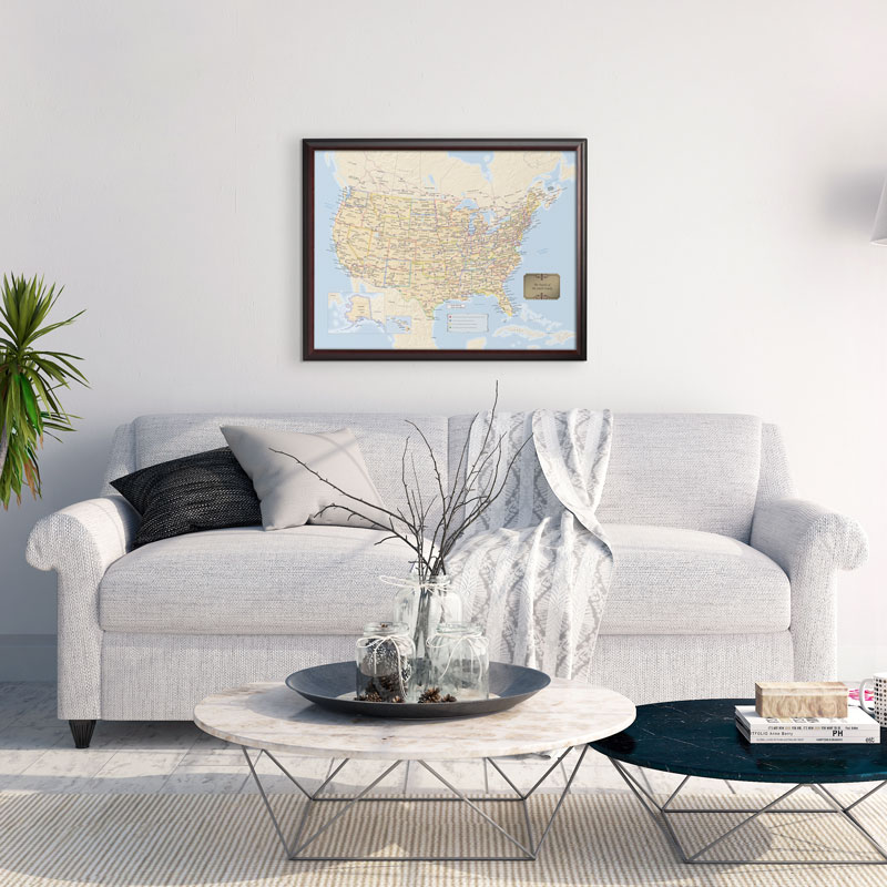 A personalized travel map of the US from Map Your Travels is seen hanging above a couch in a living room