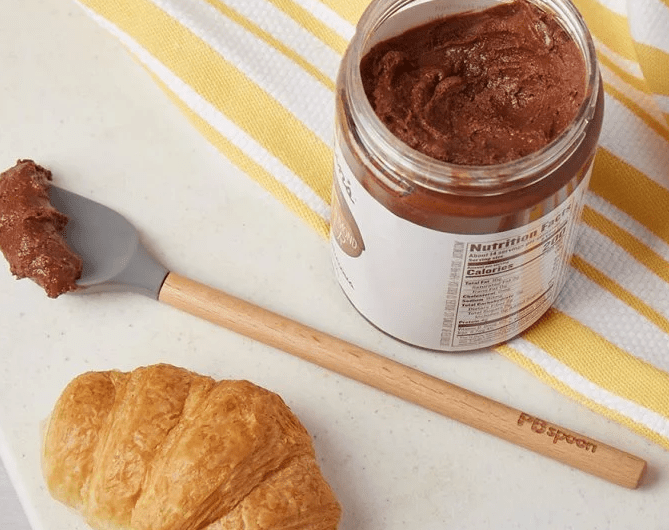 A scoop of hazelnut spread sits on a PBSpoon next to a croissant