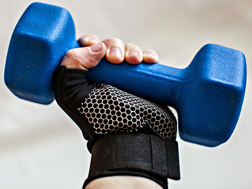 A person is seen holding a blue freeweight while wearing black fitness gloves from Wrist Assured Gloves