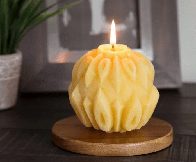 A sculpted beeswax sphere candle from Big Dipper is seen burning on a mantle