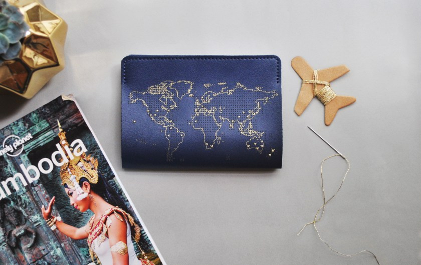 A navy stitched leather passport cover by Chasing Threads lays next to a needle & thread