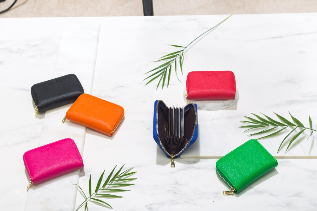 6 different colored zipper card wallets from Em John lay on a marble tabletop