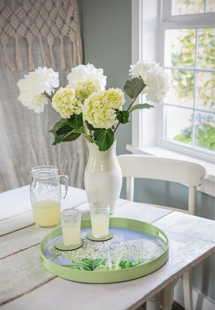 Two glasses of lemonade sit perched on a round lacquered serving tray decorated with Hydrangeas on a patio