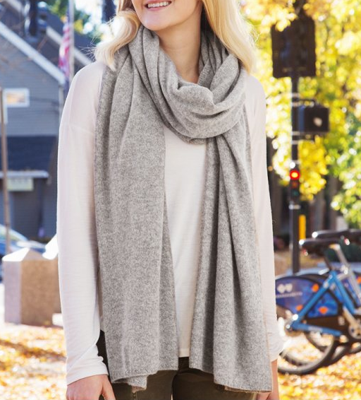 A woman is seen walking outside wearing a gray cashmere wrap from Quinn
