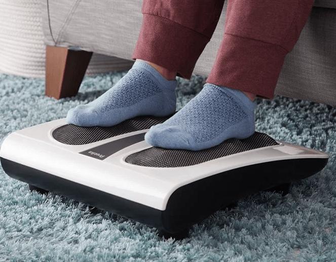 A person wearing blue socks is seen getting a thermal shiatsu foot massage with Pretika