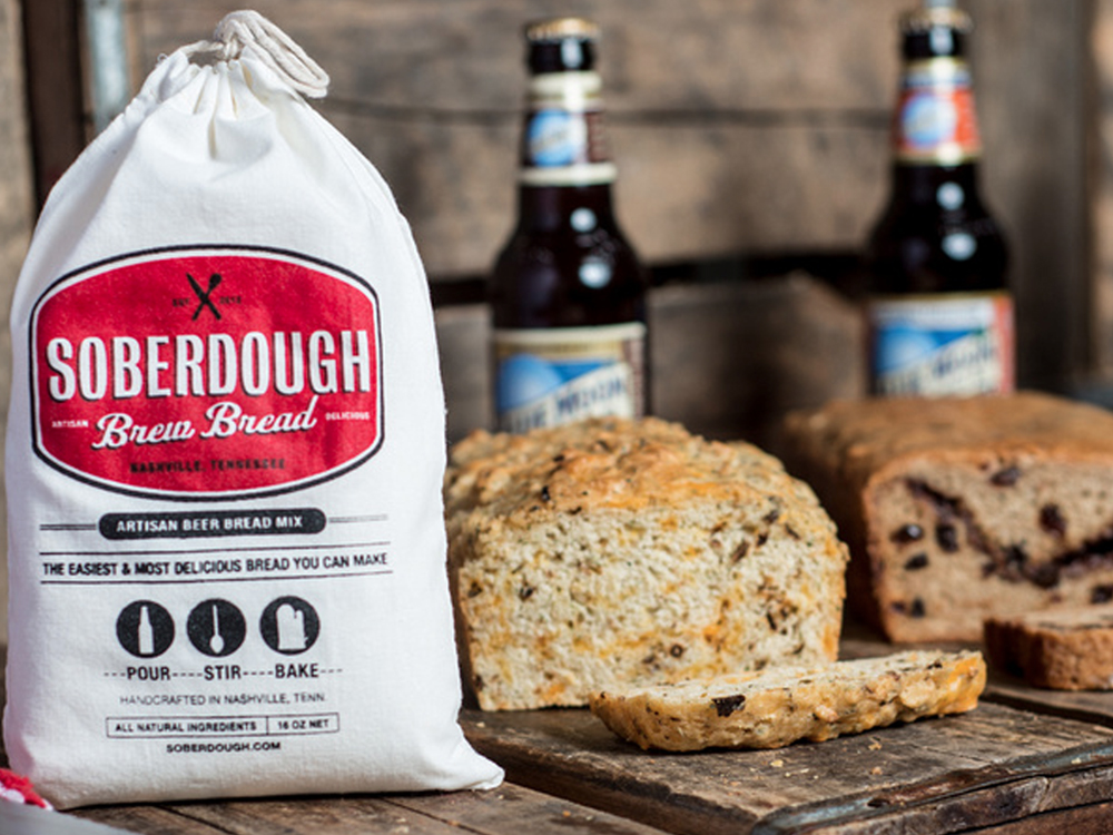 A bag of Soberdough bread mix sits on a counter in front of two baked loaves of bread.