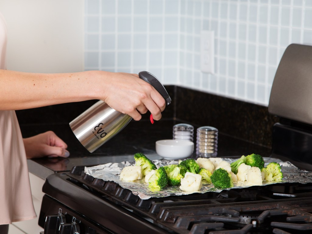 A woman is seen using her Evo stainless steel oil sprayer to spray olive oil onto broccoli & cauliflower before roasting