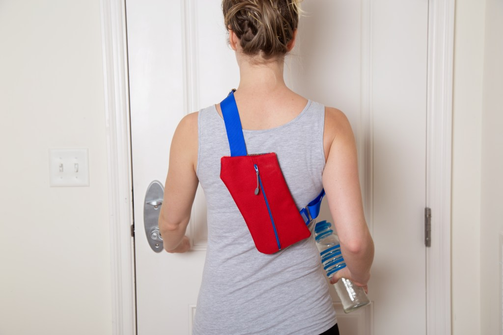 A woman is seen leaving the house carrying a water bottle and wearing a red & blue ColorPak crossbody travel bag