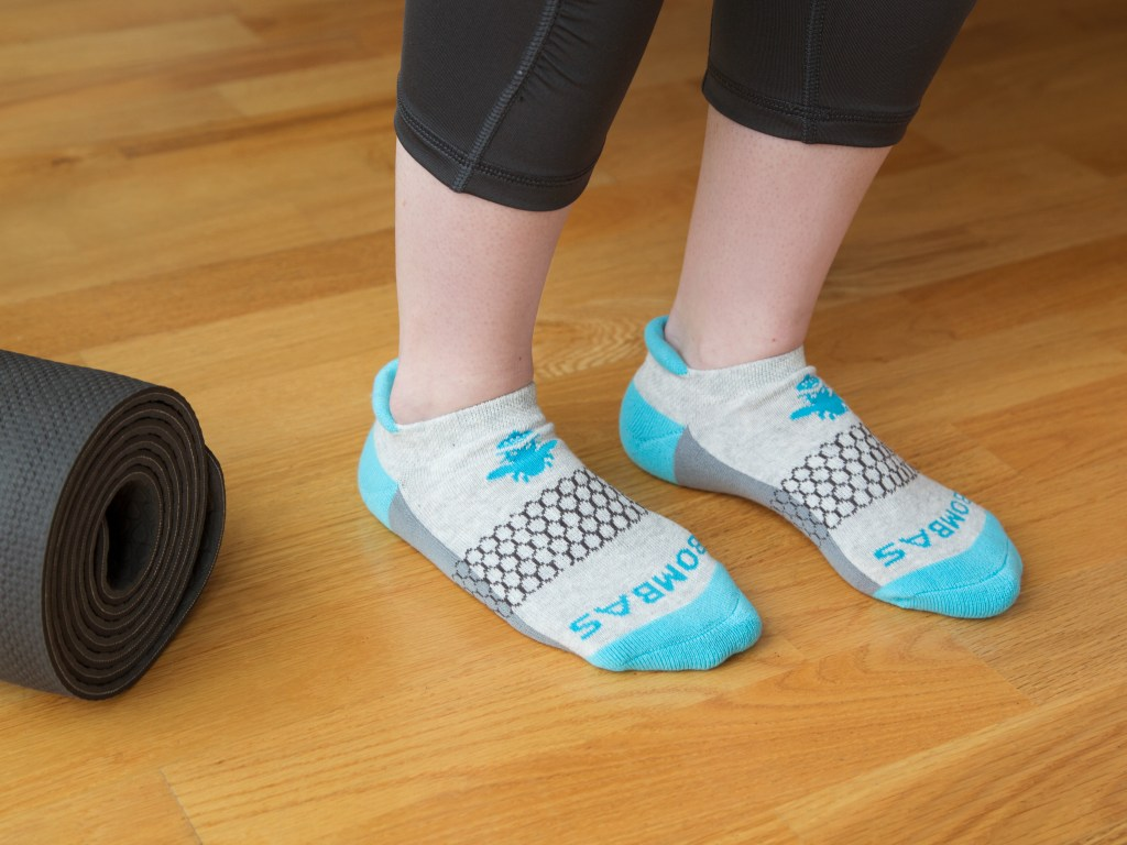 A young person is seen wearing grey & teal Bombas athleisure socks
