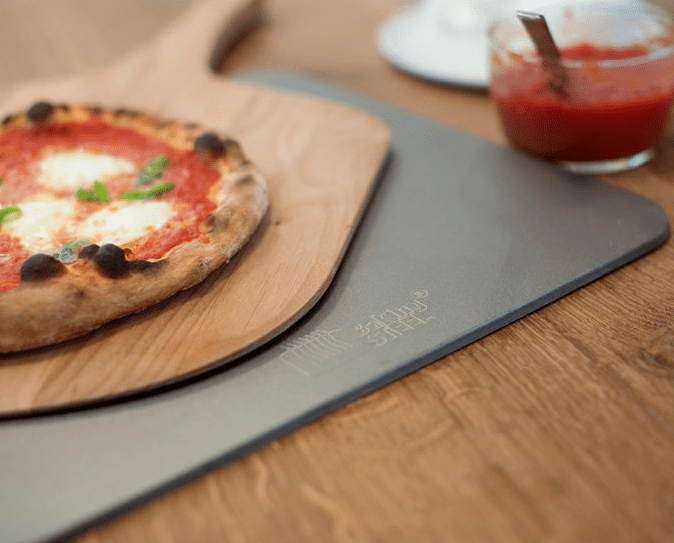 A pizza is seen sitting on a wooden paddle on top of a stainless steel baking surface from Baking Steel