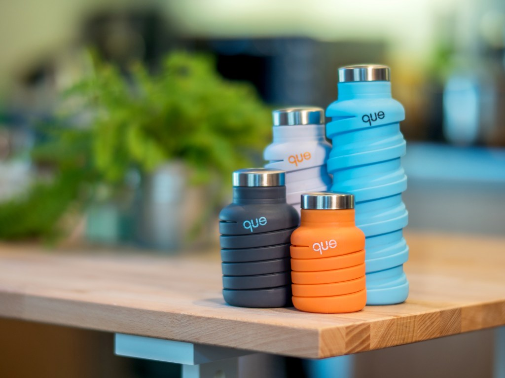 Four que collapsible silicone water bottles sit on a table