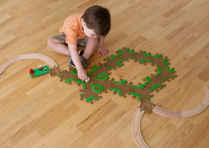 A little boy is seen playing on the floor, building an upcycled play track from Tobo Toys