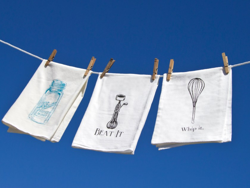 Three flour sack kitchen towels from The Coin Laundry hang on a clothesline