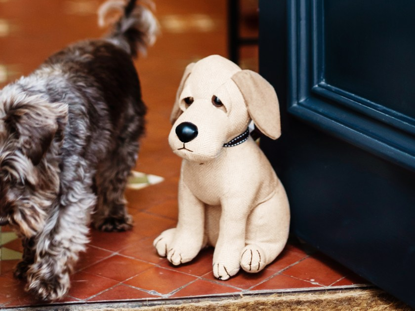 A golden whimsical dog doorstop from dora Designs is seen propping open a door as a dog walks by