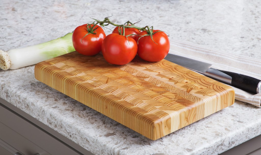 Vine-ripened tomatoes are seen sitting on an end-grain cutting board from Larch Wood