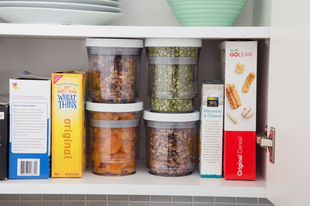 Four full Botto adjustable storage containers sit on a kitchen cabinet shelf next to cereal and crackers