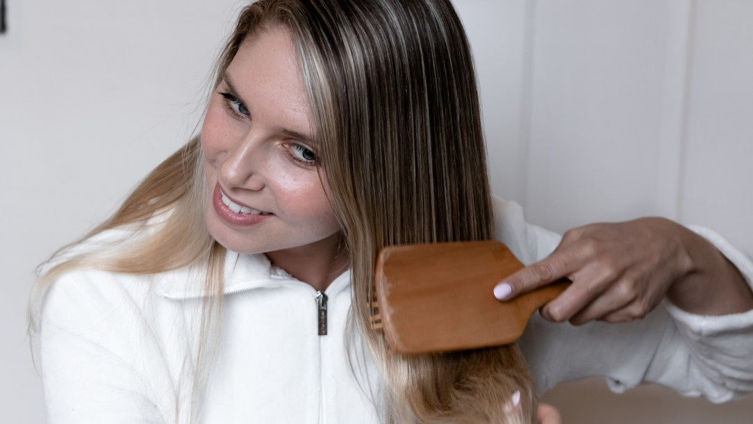 girl brushing her hair, wooden brushes for hair growth, how to grow hair faster, how to promote hair growth