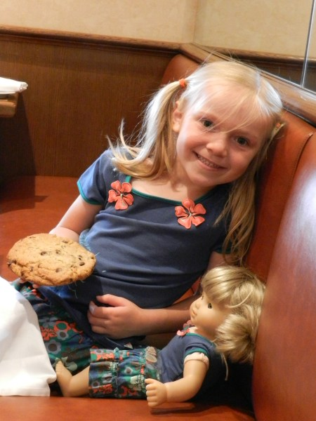 A girl and her doll wear matching outfits and are about to eat a cookie.