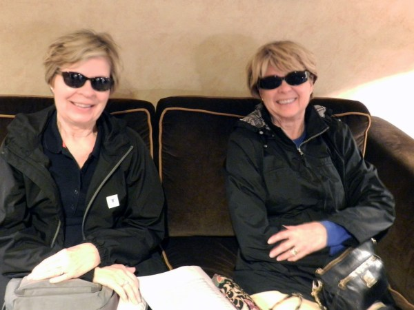 Two women with similar faces sit on the couch wearing sunglasses.