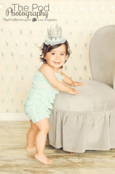 Best-First-Birthday-Cake-Smash-Photographer-Los-Angeles-Portrait-Studio-Teal-Romper-Sequins-Sparkle-Princess-Crown-Silver-Standing-Cute-Girly-Style