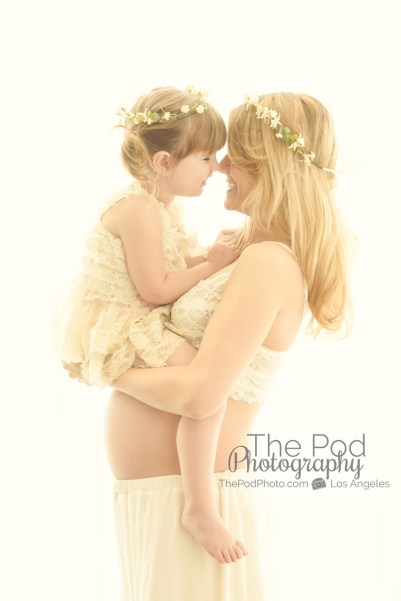 intimate-mother-and-daughter-touching-noses-daughter-is-sitting-on-moms-pregnant-stomach