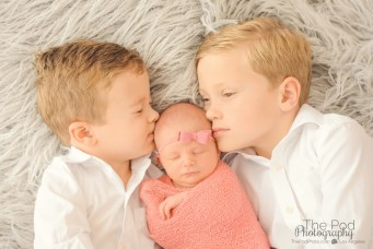 siblings-kissing-newborn-baby