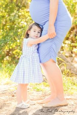 child hugging moms legs