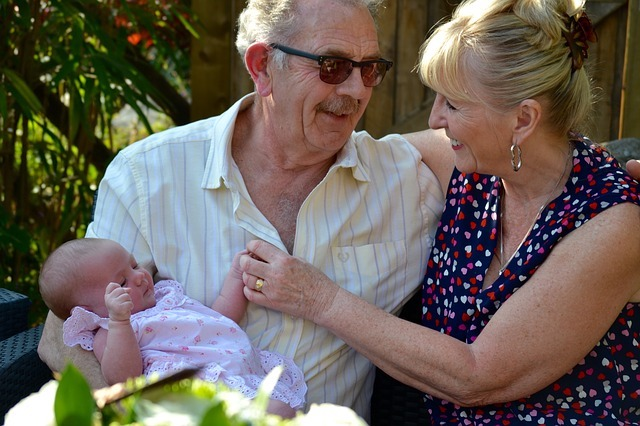 a grand father and grandmother looking happily at each other while holding a little baby.