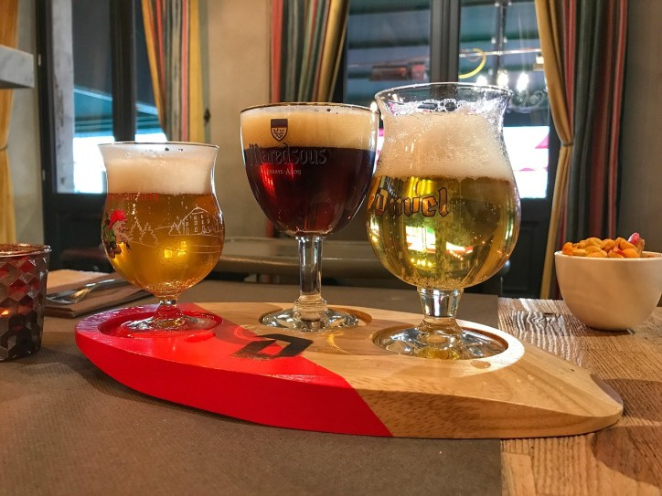 Flight of three different colored beers on a counter next to a bowl of nuts.