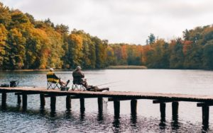 Two men sitting on a pier in the fall fishing.