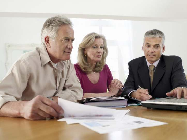 An older couple sitting at a table reviewing documents with their financial advisor.