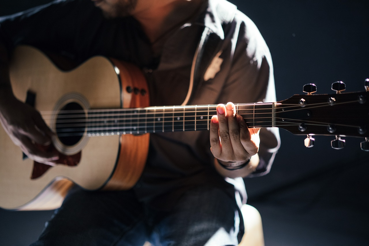 A man holding an acoustic guitar.