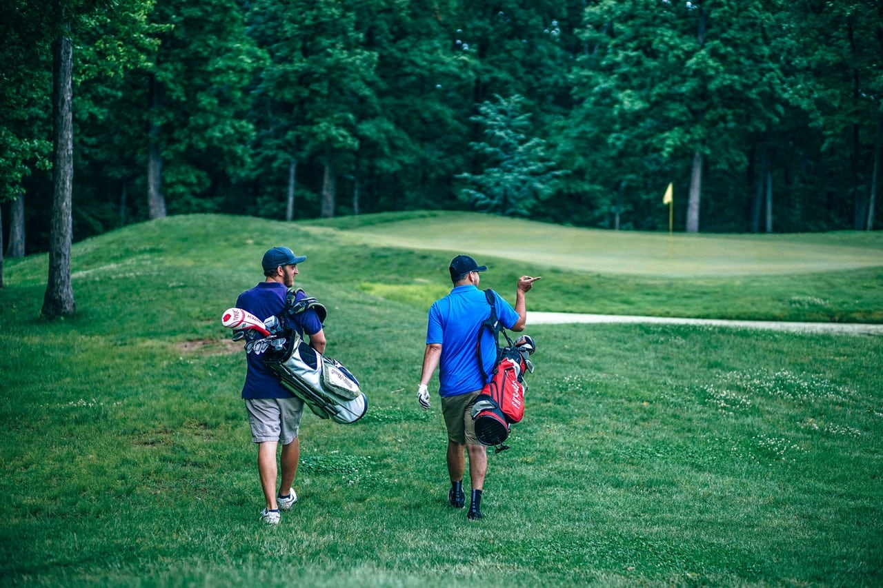 Two men holding bags of golf clubs walking across the greens.