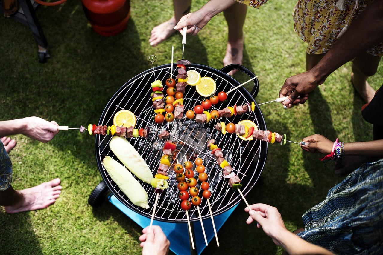 Group of friends cooking shishkabobs over an open grill.