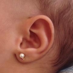 Furo na orelha do bebê. O brinco no lugar certo.
