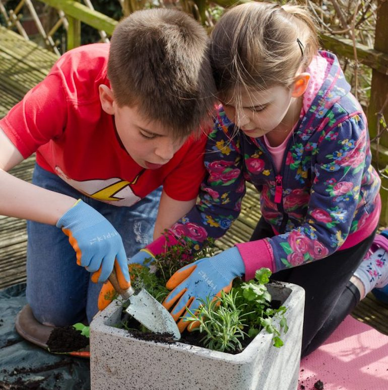 Two kids gardening in a plant pot