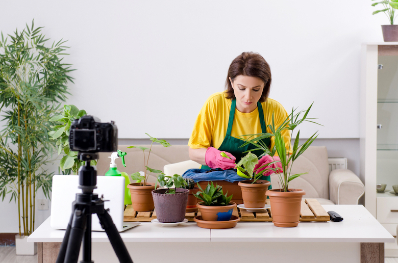 Woman filming herself repotting plants on YouTube