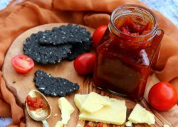 A jar of chutney, surrounded by tomatoes, cheese and biscuits