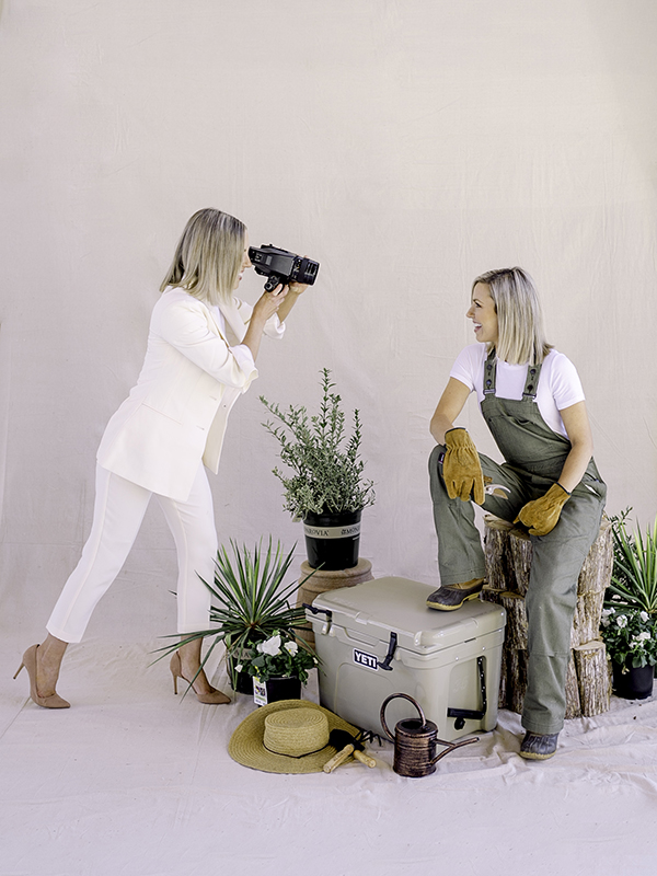 Those Plant Ladies: Heather photographing Fawn, surrounded by plants.